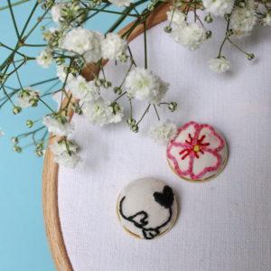 Boucle d'oreilles brodées avec un motif à fleurs dépareillées, leurs formes rappellent celles de coeur. Elles sont entièrement réalisées à la main sur un support en laiton doré.