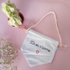 """Fanion brodée à la main avec l'inscription """"Ici on s'aime"""" soulignée d'un coeur rouge, il est cousu sur une tige en bois. Pour le fixé au mur, une cordelette en coton est noué à cette tige."""