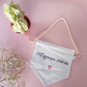 """Fanion brodée à la main avec l'inscription """"Maman chérie"""" souligné d'un coeur rouge, il est cousu sur une tige en bois. Pour le fixé au mur, une cordelette en coton est noué à cette tige."""