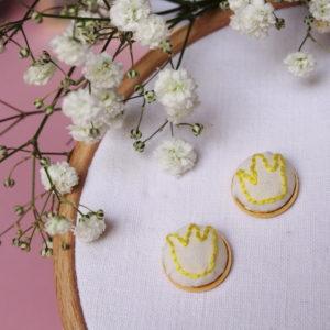 Boucle d'oreilles brodées avec un motif couronne jaune sur un support doré. Elles sont entièrement réalisées à la main ce qui les rends uniques.