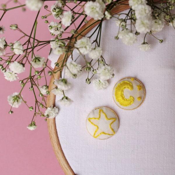 Boucle d'oreilles brodées avec un motif galaxie dépareillés, d'un coté la lune et ses étoiles, de l'autre une seule étoile. Elles sont entièrement réalisées à la main sur un support en laiton doré.