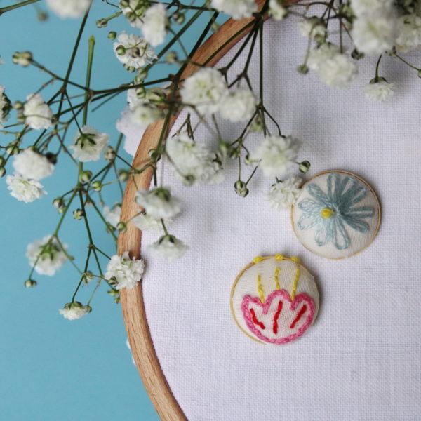 Boucle d'oreilles brodées avec un motif à fleurs dépareillées, d'un coté une rose et de l'autre une bleue. Elles sont entièrement réalisées à la main sur un support en laiton doré.