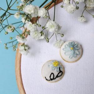 Boucle d'oreilles brodées avec un motif à fleurs dépareillées, leurs formes rappellent celles d'une edelweiss et l'autre d'une marguerite. Elles sont entièrement réalisées à la main sur un support en laiton doré.